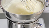 Butter cream being beaten over a bain marie
