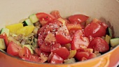 Mixed vegetables being seasoned in a pan