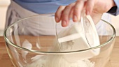 Flour and cornflour being placed in a glass bowl