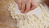 Dough ingredients being mixed with a scraper