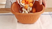 Root vegetables being added to a terracotta baking dish