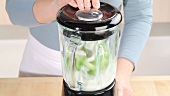 Yogurt and cucumber being pureed in a blender
