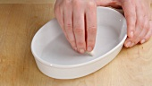 A baking dish being rubbed with garlic