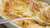 Potato gratin in a baking dish with a spoon (close-up)