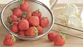 Frische Erdbeeren in einem Sieb und Schälchen mit Vanilleeis