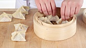 Dim sum being made: Stuffed pastry parcels being place in a bamboo basket