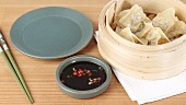 Dim sum in a bamboo basket and soy and chilli sauce