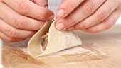 Won ton sheets being spread with egg white and filled (close-up)