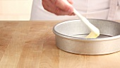 A pie dish being brushed with soft butter