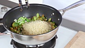 Onions and pepper being fried and rice being stirred in