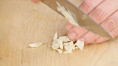 A garlic clove being finely chopped