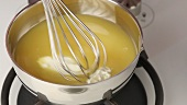 Cream cheese being added to gelatine in orange juice