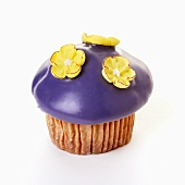 Muffin with purple icing and sugar flowers