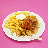 Currywurst and French fries with sauce in plate, close-up
