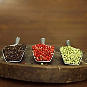 Black, red and green peppercorns in scoops