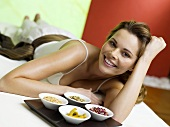 Woman lying on bed with spice in bowls, smiling