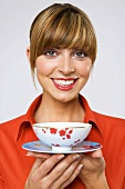 Young woman holding tea bowl, smiling, close-up