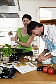Young couple in kitchen, man cutting vegetables