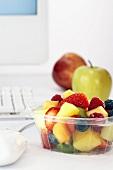 Bowl of fruit salad beside computer on office desk