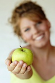 Woman holding an apple in her outstretched hand