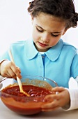 Girl (4-5) stirring tomato sauce, close-up