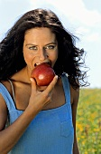 Young woman eating apple, portrait
