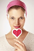 Young woman holding heart shaped lollipop, close-up, portrait
