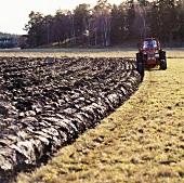 Traktor beim Pflügen auf dem Feld