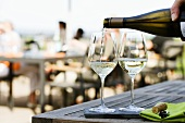 Pouring white wine on the terrace of a restaurant