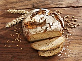 Rustic loaf of bread, partly sliced, ears & grains of wheat