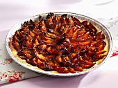 Plum tart in aluminium baking dish