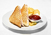 Toasted ham and cheese sandwiches with ketchup and crisps