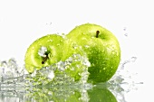 Two green apples with splashing water