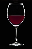 Glass of red wine against black background