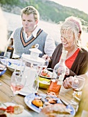 Couple sitting at table eating by lake