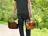 Man carrying two baskets of vegetables