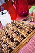Gingerbread men in rows on wicker tray, decorating ingredients