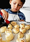 Little boy brushing cinnamon buns with butter