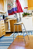 Woman on step ladder in kitchen