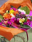Bouquet of summer flowers in orange paper