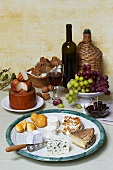 Cheese still life with red wine, grapes, nuts, bread & olives