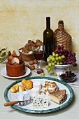 Käsestilleben mit Rotwein, Trauben, Nüssen, Brot und Oliven