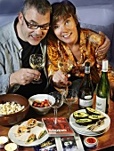 Couple watching TV with snacks and wine