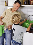 Father and son washing up in kitchen