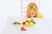 Mädchen sitzt am Tisch vor Obstteller