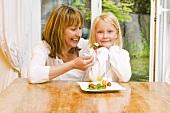 Mutter und Tochter essen Tomaten-Mozzarella-Spiesschen