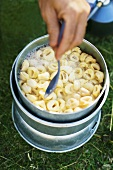 Man cooking tortellini on a camping stove