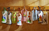 Several bibs hanging on hooks