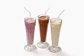 Three milkshakes in glasses with straws