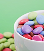 Coloured chocolate beans in bowl (close-up)